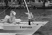 """Yachtsman Chay Blyth, trimaran Beefeater II, Tower Bridge, London 1983 before setting off on New York ��"""" San Francisco record attempt - Peter Arkell - 1980s,1983,Beefeater,boat,boats,Bridge,Chay Blyth,estuaries,estuary,London,London Bridge,male,man,marine,maritime,men,people,person,persons,PHYSICAL,river,River Thames,rivers,round-the-world,Sailing B"""