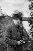 Artist John Nash 1958 pike fishing in the River Stour near his home, Wormingford Essex - Kurt Hutton - 1950s,1958,ACE,activities,artist,artists,Arts,British landscape,country,countryside,Culture,Essex,fisheries,fisherman,fishermen,fishery,fishing,fishing rod,hobbies,hobby,hobbyist,home,John Nash,leisur
