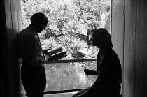 Artist John Nash 1958 leafing through a book to help identify a plant held by fellow artist Jennifer Andrews, Flatford Mill, Dedham, Suffolk where Nash taught an art course in botanical drawing - Kurt Hutton - 24-07-1958
