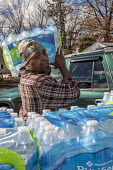 Flint, Michigan USA: World Water Day volunteers distributing 12 truckloads of bottled. The water supply was contaminated with lead nearly five years ago - Jim West - 2010s,2019,African American,African Americans,American,americans,assisting,AUTO,AUTOMOBILE,AUTOMOBILES,BAME,BAMEs,black,BME,bmes,bottle,bottled water,bottles,car,cars,contaminated,contamination,distri
