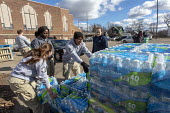 Flint, Michigan USA: World Water Day volunteers distributing 12 truckloads of bottled. The water supply was contaminated with lead nearly five years ago - Jim West - 2010s,2019,African American,African Americans,American,americans,Americorps,assisting,AUTO,AUTOMOBILE,AUTOMOBILES,BAME,BAMEs,black,BME,bmes,bottle,bottled water,bottles,car,cars,contaminated,contamina