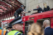 Extinction Rebellion stop DLR trains at Canary Wharf, against lack of government action on climate change. Nonviolent direct action blocking London. Police removing protestor glued onto the roof of a... - Jess Hurd - 2010s,2019,activist,activists,adult,adults,against,arrest,arrested,arresting,blocking,CAMPAIGNING,CAMPAIGNS,Canary Wharf,climate change,CLJ,DEMONSTRATING,demonstration,DEMONSTRATIONS,DLR,environment,E