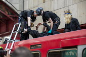 Extinction Rebellion stop DLR trains at Canary Wharf, against lack of government action on climate change. Nonviolent direct action blocking London. Police removing protestor glued onto the roof of a... - Jess Hurd - 17-04-2019