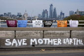 Save Mother Earth graffiti. Extinction Rebellion climate change campaigners occupy Waterloo Bridge, London - Philip Wolmuth - 2010s,2019,activist,activists,adult,adults,against,Bridge,CAMPAIGN,campaigner,campaigners,CAMPAIGNING,CAMPAIGNS,civil disobedience,Climate Change,DEMONSTRATING,demonstration,DEMONSTRATIONS,environment