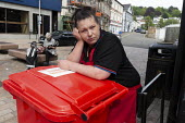 Sceptical shopworker watching Nigel Farage Brexit Party walking down the High Street Merthyr Tydfil, South Wales, Nathan Gill (R) and campaign bus - John Harris - 15-05-2019