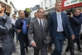 Nigel Farage Brexit Party walking down the High Street pursued by a questioning presenter Matt Frei, Merthyr Tydfil, South Wales, Nathan Gill (R) - John Harris - 2010s,2019,Brexit,Brexit Party,camera,cameras,campaign,campaigning,CAMPAIGNS,Channel 4 News,communicating,communication,DEMOCRACY,disbelief,disbelieving,election,elections,EU,European Parliament elect