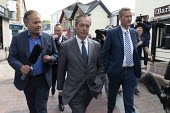 Nigel Farage Brexit Party walking down the High Street pursued by a questioning presenter Matt Frei, Merthyr Tydfil, South Wales, Nathan Gill (R) - John Harris - 2010s,2019,bodyguard,bodyguards,Brexit,Brexit Party,campaign,campaigning,CAMPAIGNS,Channel 4 News,DEMOCRACY,disbelief,disbelieving,election,elections,EU,European Parliament election,European Union,far