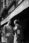 Film Director John Huston outside the famous Maxim's restaurant, Paris 1952 during a break in filming Moulin Rouge, France - Ina Bandy - 1950s,1952,ACE,ACE arts,ACTING,Actor,actors,adult,adults,Arts,break,catering,culture,directing,director,directors,entertainment,film,film making,Film Set,filming,filmmaking,films,France,french,Huston,