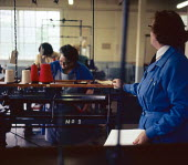 Women prisoners earning their prison allowance working in the sewing workshop, Styal Prison Wilmslow Cheshire 1959 watched by a prison wardenWomen prisoners earning their prison allowance working in t... - Malcolm Aird - 1950s,1959,CLJ,cotton,crime,employee,employees,Employment,female,HMP Styal,imprisonment,incarcerated,incarceration,inmate,inmates,jail,jailed,jails,job,jobs,justice,law,LBR,London,penal system,peniten
