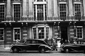 White's Private Gentlemens Club, St James's Street, London 1961. Chauffeurs and Bentley cars waiting for their employers outsideWhite's Private Gentlemens Club, St James's Street, London 1961. Chauffe... - Romano Cagnoni - 1960s,1961,AFFLUENCE,AFFLUENT,AUTO,AUTOMOBILE,AUTOMOBILES,Bentley,Bentleys,Bourgeoisie,car,cars,chauffers,chauffeur,cities,City,class,Club,clubs,communicating,communication,conversation,dialogue,drive