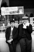 Two teenage boys leaning on a shop front Soho London 1961Two teenage boys leaning on a shop front Soho London 1961Two teenage boys leaning on a shop front Soho London 1961Two teenage boys leaning on a... - Romano Cagnoni - 1960s,1961,adolescence,adolescent,adolescents,boy,boys,child,CHILDHOOD,children,cities,City,Cornflakes,Daz,flat cap,friend,friends,friendship,friendships,juvenile,juveniles,kid,kids,leisure,LFL,LIFE,L