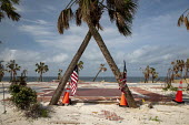 Mexico Beach, Florida, USA: Palm trees and flags where a beach house was destroyed. Destruction from Hurricane Michael 7 months after the storm hit the Florida Panhandle - Jim West - 2010s,2019,America,american,americans,beach,BEACHES,CLIMATE,Climate Change,coast,coastal,coasts,conditions,damage,damaged,destroyed,destruction,devastation,DIA,Disaster,disasters,extreme weather,flag,