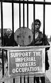 Imperial Typewriters factory occupation Hull 1975. Helen Charlesworth inside the locked gates of the plant occupied by the striking workforce as they resisted its closure by an American multinational - John Sturrock - 1970s,1975,against,American,americans,close,closed,closing,closure,closures,dispute,disputes,Equal Pay,FACTORIES,factory,FEMALE,gate,gates,Helen Charlesworth,Hull,Imperial typewriters,Industrial dispu