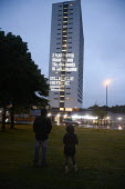 Projection of a message about tower block fire safety by Grenfell United onto Cruddas Park Tower, Newcastle Upon Tyne. 2 Years After Grenfell And The Fire Doors in this Building Still Aren't Fit For P... - Mark Pinder - 12-06-2019