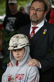 Chris Kitchen NUM and child wearing Pit Helmet, Orgreave 35th Anniversary Rally, Orgreave, Sheffield, South Yorkshire - John Harris - 2010s,2019,activist,activists,against,Anniversary,Battle of Orgreave,CAMPAIGNING,CAMPAIGNS,COMMEMORATE,COMMEMORATING,commemoration,COMMEMORATIONS,commemorative,DEMONSTRATING,Demonstration,Gen Sec,helm