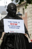 The Time Is Now - Christian Aid protest and lobby of Parliament calling for urgent action on climate change. Protestors place a placard on the statue of Mahatma Gandhi in Parliament SquareThe Time Is... - Stefano Cagnoni - 26-06-2019