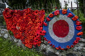 World War Memorial poppies, Yarn bombing or guerrilla knitting in Llwyngwril, the quirky little Welsh village knits creations through the winter as a community project to decorate the village in the s... - Jess Hurd - 2010s,2019,ACE,armed,armed forces,art,arts,BOMB,bombing,bombings,BOMBS,Cambrian Coast,Coast,coastal,coasts,communities,community,crochet,culture,decorate,floral tribute,floral tributes,flower,flowerin