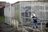 Banksy Graffiti on a garage, Port Talbot, Wales - Paul Box - 2010s,2019,ACE,art,arts,artwork,artworks,Banksy,boy,boys,child,CHILDHOOD,children,culture,factory,garage,graffiti,juvenile,juveniles,kid,kids,male,mural,murals,Painting,paintings,people,plant,Port,por