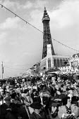 British holidaymakers in deckchairs, crowded seafront Blackpool 1965 - Romano Cagnoni - 1960s,1965,adult,adults,age,ageing population,Blackpool,Blackpool Tower,busy,COAST,coastal,coasts,crowd,crowded,deckchairs,elderly,full,holiday,holiday maker,holiday makers,holiday resort,holidaymaker