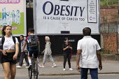 Obesity is a cause of cancer too advertisement Cancer Research UK obesity campaign, which highlights excess weight as a cause of cancer. The billboard looks like a cigarette packet. Some members of th... - John Harris - 2010s,2019,advertisement,advertisements,advertising,BAME,BAMEs,billboard,billboards,Black,BME,bmes,bodies,body,campaign,campaigning,CAMPAIGNS,cancer,CANCERS,charitable,charity,diversity,ethnic,ethnici