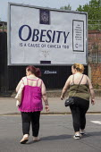 Obesity is a cause of cancer too advertisement Cancer Research UK obesity campaign, which highlights excess weight as a cause of cancer. The billboard looks like a cigarette packet. Some members of th... - John Harris - 16-07-2019