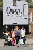 Obesity is a cause of cancer too advertisement Cancer Research UK obesity campaign, which highlights excess weight as a cause of cancer. The billboard looks like a cigarette packet. Some members of th... - John Harris - 2010s,2019,advertisement,advertisements,advertising,Asian,Asians,BAME,BAMEs,billboard,billboards,Black,BME,bmes,bodies,body,campaign,campaigning,CAMPAIGNS,cancer,CANCERS,charitable,charity,diversity,e