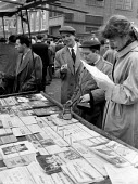 Berliner Ensemble first visit to UK to stage Mother Courage by Bertolt Brecht London 1956. Ernst Busch holding cigarette, Heinz Schubert and Elisabeth Goebel looking at sheet music in Petticoat Lane s... - Alan Vines - 1950s,1956,1st,ACE,ACTING,Actor,actors,adult,adults,arts,Berliner Ensemble,Bertolt Brecht,Brecht,cigarette,CIGARETTES,cities,City,culture,Elisabeth Goebel,Ensemble,entertainment,Ernst Busch,FAMILY,FEM
