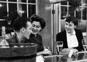 Berliner Ensemble first visit to UK to stage Mother Courage by Bertolt Brecht London 1956. Ronnie Ayres chatting in a pub with Kaete Ruelicke and Isot Killan (R) of the Ensemble - Alan Vines - 1950s,1956,1st,ACE,ACTING,Actor,actors,adult,adults,alcohol,Berliner Ensemble,Bertolt Brecht,Brecht,CHAT,chatting,cities,City,communicating,communication,conversation,conversations,culture,dialogue,En