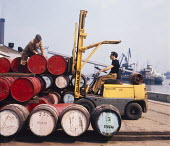 Dockers unloading cargo imported from Spain, Tilbury Docks Essex 1970 - Chris Davies - 1970,1970s,barrel,barrels,boat,boats,by hand,capitalism,cargo,Coventry Climax,dock,DOCK WORKER,DOCK WORKERS,docker,dockers,docks,dockside,dockworker,dockworkers,DRIVER,DRIVERS,EBF,Economic,Economy,emp
