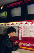 Man placing bet, Ladbrokes betting shop 1989 - John Harris - 1980s,1989,bet,BETS,betting,Betting Shop,betting slip,business,domesticated ungulates,EBF,Economic,Economy,equestrian,equine,form,gamble,gambling,HORSE,horses,Ladbrokes,male,man,men,odds,people,person