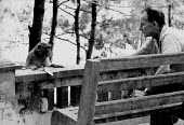 Journalist James Cameron trying to feed a monkey whilst on a working trip to North Vietnam during the Vietnam War 1964 - Romano Cagnoni - 1960s,1964,ACE,Arts,Cameron,Culture,employee,employees,Employment,James Cameron,job,jobs,journalism,journalist,journalists,LBR,Leisure,LFL,LIFE,male,man,media,men,monkey,outdoors,Park,parks,people,per