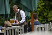 Waiter serving drinks, Lords Of The Manor Hotel, Upper Slaughter - John Harris - 2010s,2019,AFFLUENCE,AFFLUENT,Bourgeoisie,drink,drinker,drinkers,drinking,drinks,EBF,Economic,Economy,elite,elitism,employee,employees,Employment,high,high income,Hospitality,hotel,hotels,income,INEQU