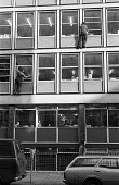 Window cleaners with no safety harness perched on window ledges cleaning windows of central London office 1974 - Chris Davies - 29-04-1974