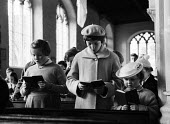 Aldeburgh Suffolk 1957. Young sisters (R) in their Sunday best clothes singing from hymn books at a Church of England morning church service - Kurt Hutton - 1950s,1957,Anglican,belief,BOOK,books,child,CHILDHOOD,children,Christian,christianity,christians,church,Church of England,church service,churches,clothes,Cof E,cofe,congregation,conviction,faith,femal