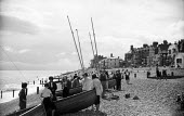 Small sailing yachts on the beach, Aldeburgh Regatta Suffolk 1957 - Kurt Hutton - 1950s,1957,beach,BEACHES,boat,boats,COAST,hobbies,hobby,hobbyist,holiday,holiday maker,holiday makers,holidaymaker,holidaymakers,holidays,leisure,LFL,LIFE,lifestyle,mast,masts,OCEAN,PEOPLE,person,pers