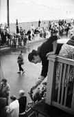 Young woman on a balcony along the seafront retrieving her dropped flag while waiting for the Aldeburgh Carnival Suffolk 1957 - Kurt Hutton - 1950s,1957,carnival,Carnivals,COAST,FEMALE,holiday,holiday maker,holiday makers,holidaymaker,holidaymakers,holidays,leisure,LFL,LIFE,lifestyle,OCEAN,parade,PEOPLE,person,persons,RECREATION,RECREATIONA