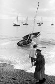 Small sailing yachts on the beach, Aldeburgh Regatta Suffolk 1957 - Kurt Hutton - 1950s,1957,beach,BEACHES,boat,boats,COAST,FEMALE,hobbies,hobby,hobbyist,holiday,holiday maker,holiday makers,holidaymaker,holidaymakers,holidays,leisure,LFL,LIFE,lifestyle,male,man,mast,masts,men,OCEA