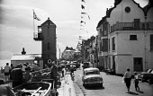 Aldeburgh High street at the end of the annual Carnival and Regatta Suffolk 1957 - Kurt Hutton - 1950s,1957,Aldeburgh,AUTO,AUTOMOBILE,AUTOMOBILES,beach,BEACHES,bunting,car,cars,COAST,FEMALE,High Street,holiday,holiday maker,holiday makers,holidaymaker,holidaymakers,holidays,leisure,LFL,LIFE,lifes