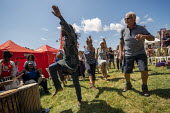 Unison dancing, Tolpuddle Martyrs Festival, Dorset. Passing PCS tents - Jess Hurd - 2010s,2019,BAME,BAMEs,Black,Black and White,BME,bmes,dance,dancer,dancers,dancing,diversity,Dorset,ethnic,ethnicity,Festival,FESTIVALS,Kevin McGuire,Matt Collins about fighting racism and fascism,melo