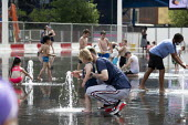 Heatwave. Children playing with water jets, Centenary Square, Birmingham, reflection pool with fountains - John Harris - 2010s,2019,BAME,BAMEs,Birmingham,Black,Black and White,BME,bmes,care,caring,CHILD,CHILDHOOD,Children,clean,DAD,DADDIES,DADDY,DADS,daughter,DAUGHTERS,diversity,ethnic,ethnicity,FAMILY,father,FATHERHOOD