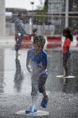 Heatwave. Children playing with water jets, Centenary Square, Birmingham, reflection pool with fountains - John Harris - 2010s,2019,BAME,BAMEs,Birmingham,Black,BME,bmes,boy,boys,child,CHILDHOOD,Children,clean,diversity,ethnic,ethnicity,fountain,fountains,having fun,heat,holiday,holidays,hot,juvenile,juveniles,kid,kids,L