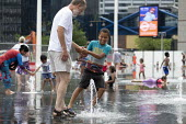 Heatwave. Children playing with water jets, Centenary Square, Birmingham, reflection pool with fountains - John Harris - 2010s,2019,BAME,BAMEs,Birmingham,Black,Black and White,BME,bmes,boy,boys,child,CHILDHOOD,Children,clean,DAD,DADDIES,DADDY,DADS,diversity,ethnic,ethnicity,FAMILY,father,FATHERHOOD,fathers,fountain,foun