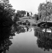 A horse reflected in water Stone Lodge Ipswich Suffolk 1957 - Kurt Hutton - 1950s,1957,building,buildings,calm,Domesticated Ungulates,English heritage,ENI,environment,environmental Issues,equestrian,equine,folk,heritage,home,homes,horse,HORSES,house,houses,Housing,idyll,idyll