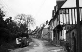 Man making deliveries from his van to the houses in the mediaeval village of Lavenham Suffolk 1958 - Kurt Hutton - 1950s,1958,baker,bakers,bakery,building,buildings,country,countryside,deliveries,delivering,delivery,driver,drivers,DRIVING,EBF,Economic,Economy,employee,employees,Employment,English heritage,ENI,envi