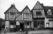 Woman walking into the Post Office on the High Street in the mediaeval village of Lavenham Suffolk 1958. The Crooked House - Kurt Hutton - 1950s,1958,bicycle,bicycles,BICYCLING,Bicyclist,Bicyclists,bike,bikes,bought,building,buildings,buying,consumer,consumers,country,countryside,customer,customers,CYCLE,CYCLING,Cyclist,Cyclists,EBF,Econ
