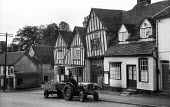 Farmhand with tractor and produce passing The Crooked House in the mediaeval village of Lavenham Suffolk 1958 - Kurt Hutton - 1950s,1958,agricultural,agriculture,building,buildings,capitalism,country,countryside,EBF,Economic,Economy,employee,employees,Employment,English heritage,ENI,environment,environmental Issues,farm,farm