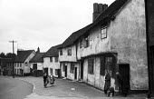 Women talking and laughing together outside their homes in the mediaeval village of Lavenham Suffolk 1958 - Kurt Hutton - 1950s,1958,building,buildings,CHAT,chatting,child,CHILDHOOD,CHILDREN,communicating,communication,communities,community,conversation,conversations,country,countryside,dialogue,English heritage,ENI,envi