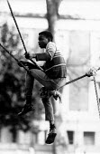 Teenage boy playing on ropes, adventure playground, Notting Hill West London 1970Teenage boy playing on ropes, adventure playground, Notting Hill West London 1970Teenage boy playing on ropes, adventur... - Clive Capel - 14-05-1970