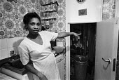 Resident pointing to asbestos in her kitchen cupboard, Wandsworth, South London 1983 - NLA - 1980s,1983,Asbestos,ASBESTOSIS,BAME,BAMEs,Black,blocks,BME,bmes,Council Housing,Council Housing,danger,dangerous,dangers,diversity,ethnic,ethnicity,FEMALE,flat,flats,hazard,hazardous,HAZARDS,HEA,Healt