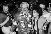 Anti-apartheid activist David Kitson arriving at London Airport, 1984, having been released after 20 years in prison in South Africa, welcomed by his wife Norma, family and supporters, he was convicte... - NLA - 1980s,1984,AAM,Africa,air transport,airline,Airport,AIRPORTS,ANC,Anti Apartheid Movement,Apartheid,armed,ARRIVAL,arrivals,arrive,arrives,arriving,bomb,BOMBS,camera,cameras,communicating,communication,
